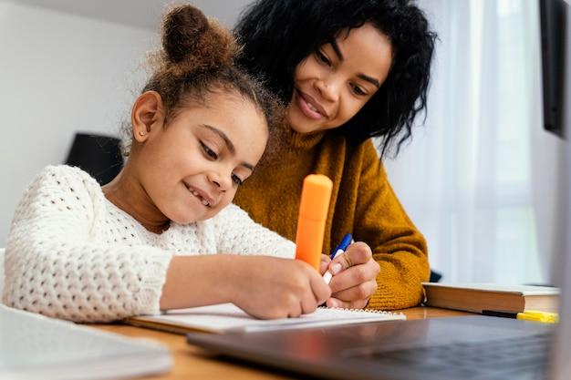 Klein meisje thuis tijdens online school hulp krijgen van haar grote zus Premium Foto