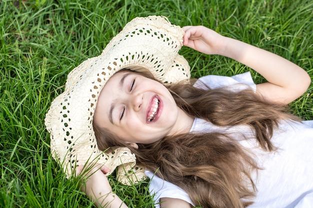 Klein meisje tot in het gras. zomertijd en zonnige dag Gratis Foto