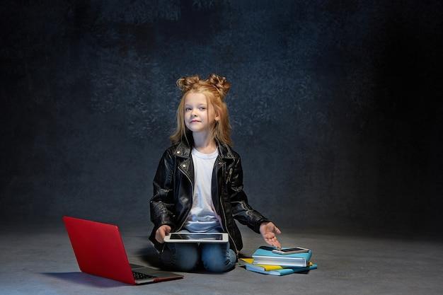 Klein meisje zit met laptop, tablet en telefoon in grijze studio Gratis Foto