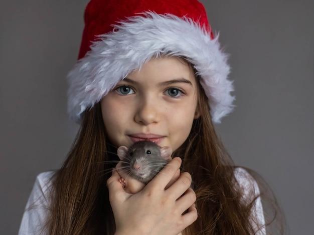 Klein mooi meisje in een new years-pet houdt in haar handen een decoratief binnenlands rat-symbool van nieuwjaarsportret Premium Foto