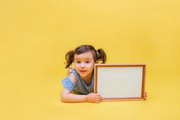 Klein mooi meisje met vlechten met een banner voor reclame op geïsoleerd geel Premium Foto