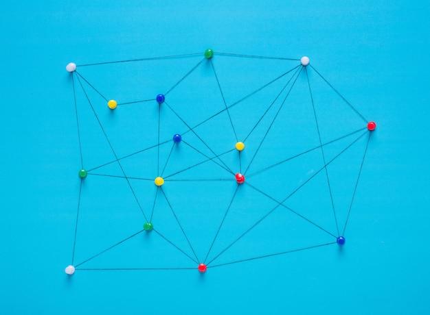 Klein netwerk van punaiseaansluitingen opstelling van kleurrijke pinnen gekoppeld aan een touwtje Premium Foto