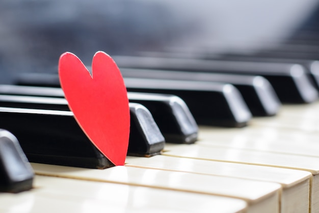 Klein rood hart op pianotoetsenbord. concept liefde, valentijnsdag Premium Foto