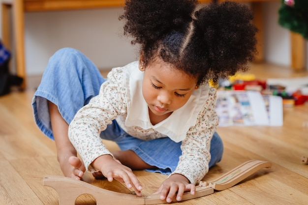 Klein schattig kind meisje genieten van houten puzzel spelen op de houten vloer thuis in de woonkamer. Premium Foto