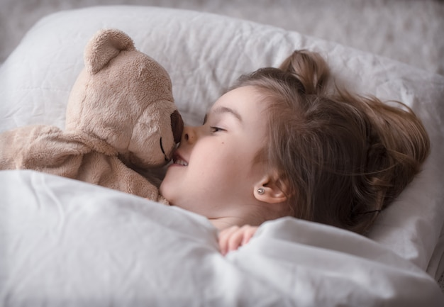Klein schattig meisje in bed met speelgoed Gratis Foto