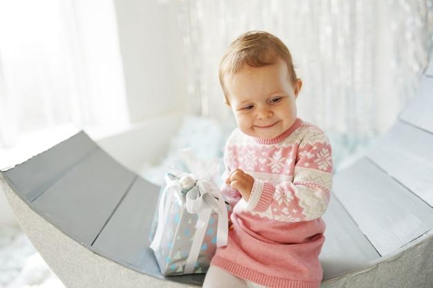 Klein schattig meisje in de trui met kerstcadeau doos Premium Foto