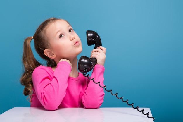 Klein schattig meisje in roze shirt met aap en blauwe broek praat via de telefoon Premium Foto