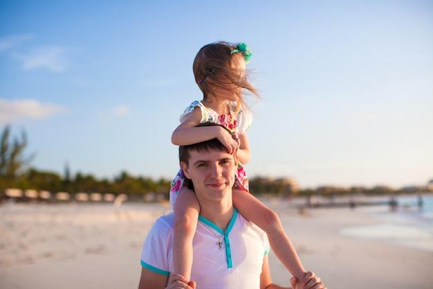 Klein schattig meisje rijden op haar vader wandelen langs het strand Premium Foto