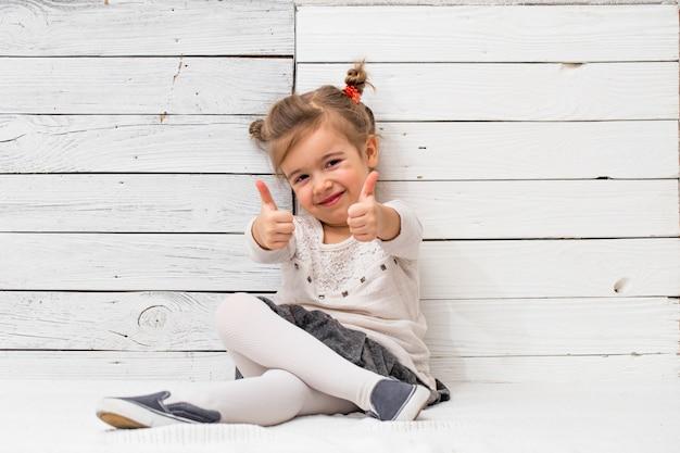 Klein schattig meisje school meisje, zittend op wit hout Gratis Foto