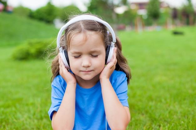 Klein schattig meisje zit in een park luisteren naar muziek in witte koptelefoon Premium Foto