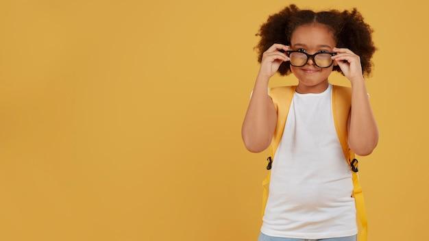 Klein schoolmeisje dat haar exemplaarruimte van het leesbril schikt Gratis Foto