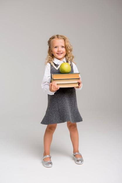 Klein schoolmeisje met boeken op een lichte achtergrond Premium Foto