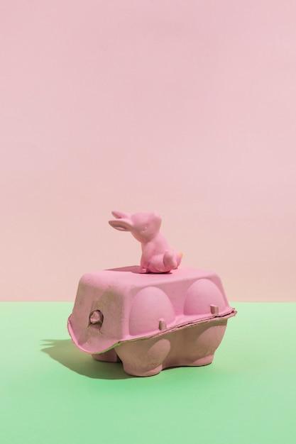 Klein stuk speelgoed konijn op eierrek op lijst Gratis Foto
