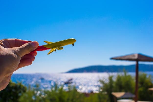 Klein vliegtuig in vrouwelijke hand op achtergrond van blauwe hemel Premium Foto