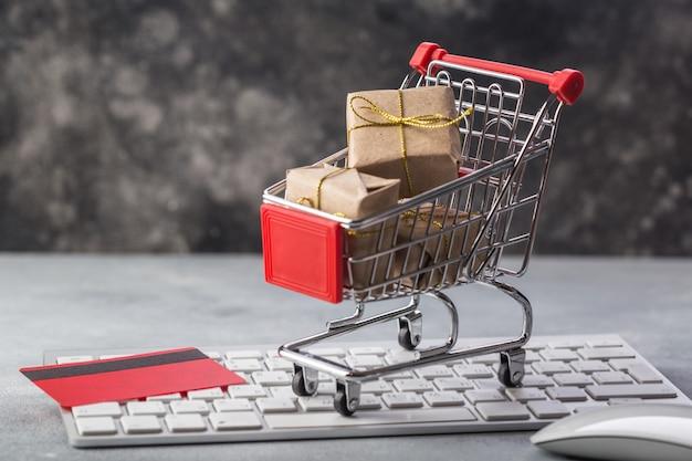 Klein winkelwagentje met cadeautjes en creditcard op een laptop toetsenbordconcepten Premium Foto