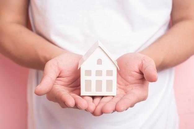 Klein wit huis op menselijke hand Premium Foto