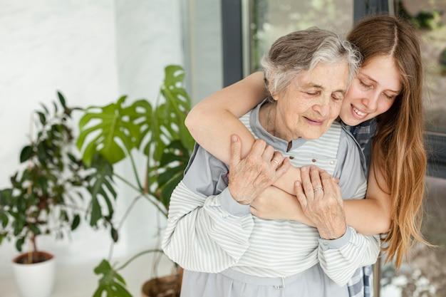 Kleindochter die haar grootmoeder omhelst Gratis Foto