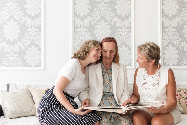 Kleindochter die oma koestert die fotoalbum thuis kijkt Gratis Foto