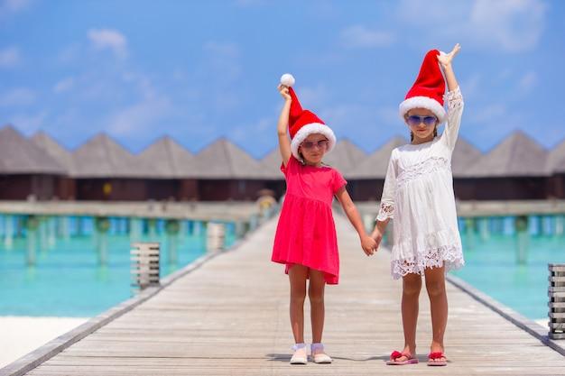 Kleine aanbiddelijke meisjes in kerstmanhoeden tijdens strandvakantie bij houten pier Premium Foto
