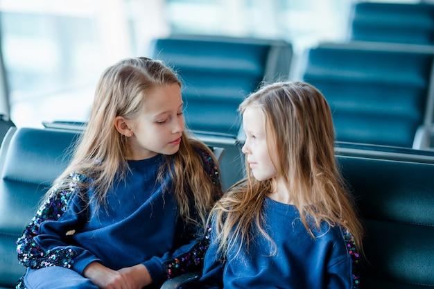 Kleine aanbiddelijke meisjes in luchthaven dichtbij groot venster Premium Foto
