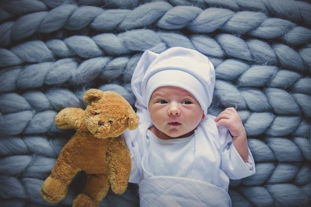 Kleine baby draagt een witte kleding en hoed met taddy beer Premium Foto