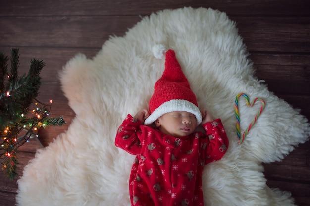 Kleine baby in rode dop van de kerstman viert kerstmis Premium Foto