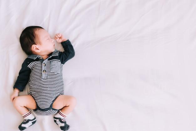 Kleine baby slapen op zacht wit bed in de slaapkamer - gelukkige familie momenten Premium Foto