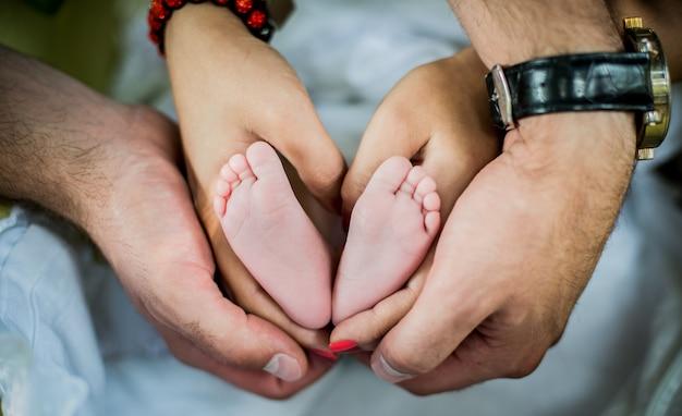 Kleine baby voet in handen van de ouders Premium Foto