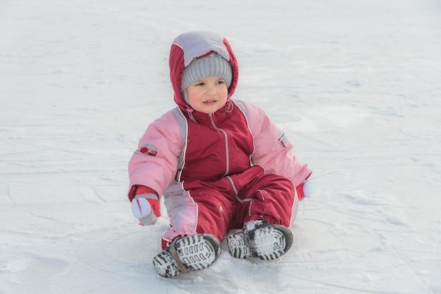 Kleine baby zit op ijs in de winter Premium Foto