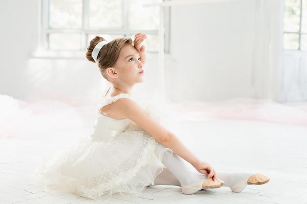 Kleine balerina in witte tutu in de klas op balletschool Gratis Foto