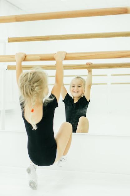 Kleine ballerina meisje in het zwart. aanbiddelijk kind dat klassiek ballet in een witte studio danst. kinderen dansen. kinderen optreden. jonge begaafde danser in een klas. preschool kind kunst lessen nemen. Premium Foto