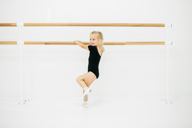 Kleine ballerina meisje in het zwart. schattig kind klassiek ballet dansen. kinderen dansen. kinderen optreden. jonge begaafde danser in een klas. preschool kind kunst lessen nemen. Premium Foto