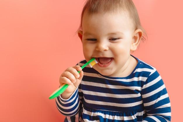 Kleine beautifulbaby-peuter schoonmakende tanden met kindborstel op roze achtergrond Premium Foto