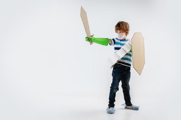 Kleine blanke jongen als een krijger in gevecht met een pandemie van het coronavirus, met een schild, een speer en een bandoleer van toiletpapier, aanvallend Gratis Foto