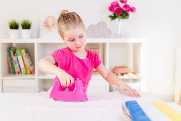 Kleine blonde babymeisje huisvrouw spelen met speelgoed roze ijzer. ironongkleren op een witte lijst. huishoudelijk werk, helper Premium Foto
