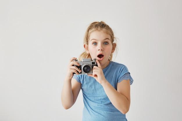 Kleine blonde juffrouw met blauwe ogen nam familiefoto van ouders met filmcamera toen vader uitgleed en viel. kind kijkt bang dat ouder gewond raakt. Gratis Foto