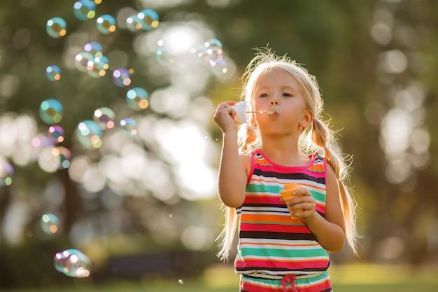 Kleine blonde meisje blaast zeepbellen in de zomer op een wandeling Premium Foto