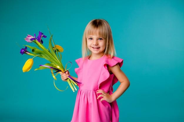 Kleine blonde meisje lacht in een roze jurk en met een boeket van lentebloemen op een blauwe ruimte isoleren Premium Foto