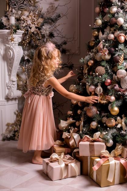 Kleine blonde meisje siert kerstboom in een prachtig interieur Premium Foto