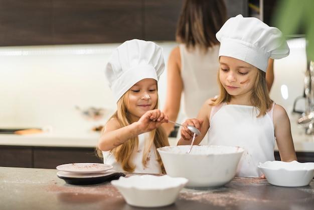 Kleine broers en zussen in chef-kok hoed mengen ingrediënten in kom op keuken aanrecht Gratis Foto