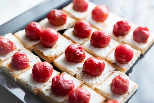 Kleine broodjes met kaas en gegrilde kersentomaat. Premium Foto