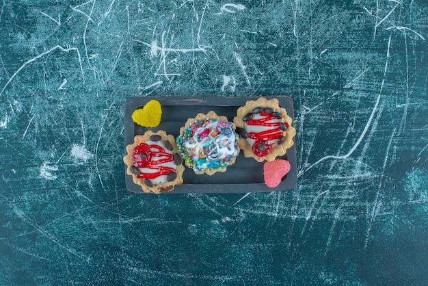 Kleine bundel van cupcakes en marmelade op een schotel op blauwe achtergrond. hoge kwaliteit foto Gratis Foto