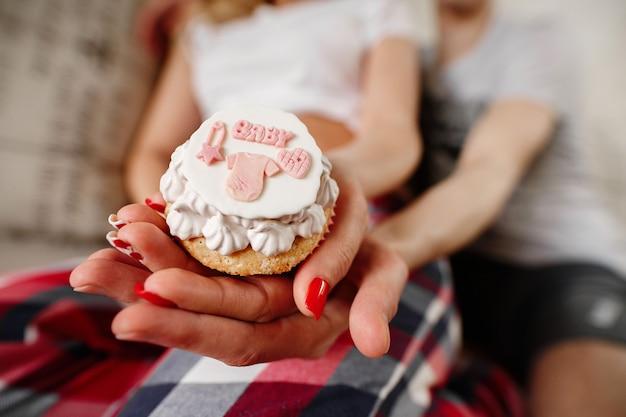 Kleine cake voor een pasgeboren meisje. de toekomstige ouders wachten baby. jong gezin in afwachting van de geboorte van een kind. Premium Foto