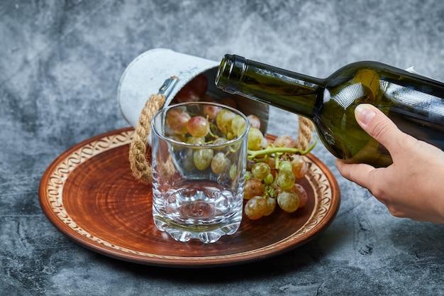Kleine emmer met druiven in keramische plaat en hand gieten wijn in het glas op marmer. Gratis Foto