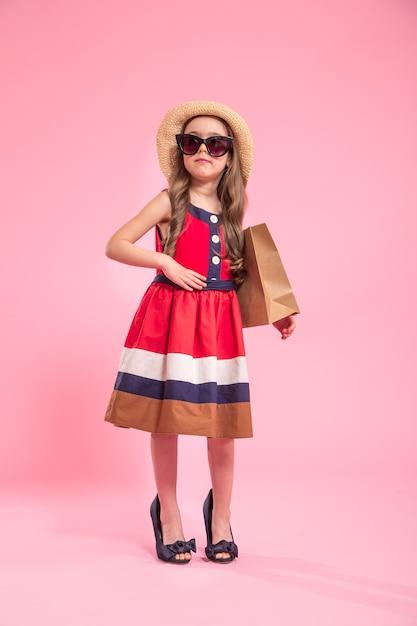 Kleine fashionista met een boodschappentas in een zomerhoed en bril, op een gekleurde roze achtergrond in moeders schoenen, het concept van kindermode Gratis Foto