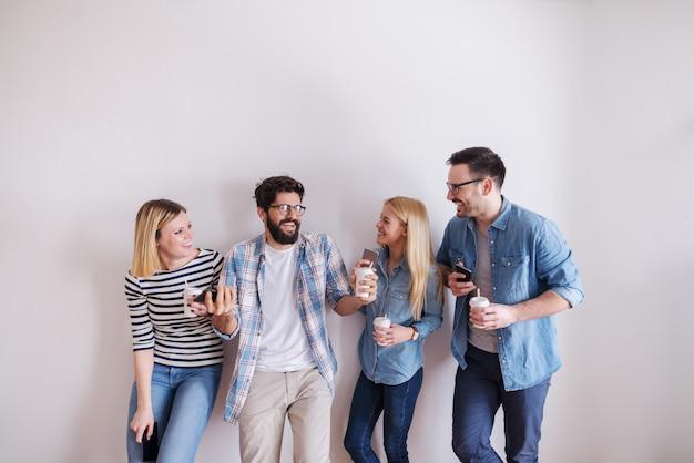 Kleine groep jonge zakenlui die koffie houden om te gaan en slimme telefoons terwijl het spreken en het lachen. op de achtergrond terwijl muur. start bedrijfsconcept. Premium Foto