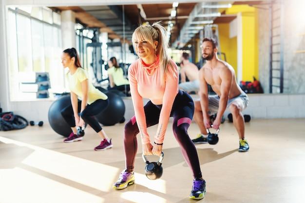Kleine groep mensen met gezonde gewoonten swingende kettlebell. gym interieur, spiegel in de achtergrond. man Premium Foto