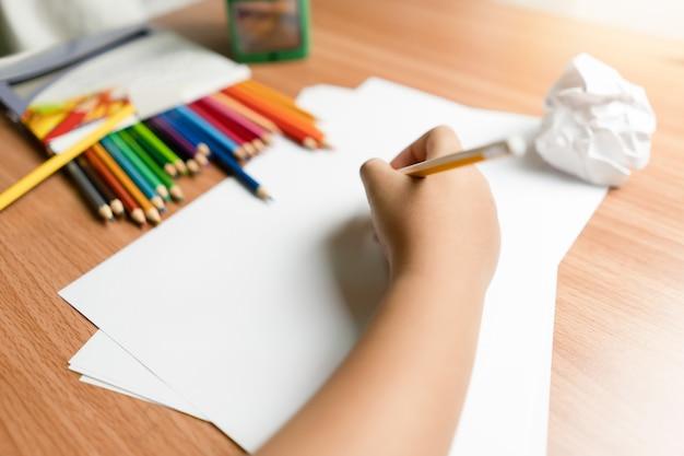 Kleine hand van kind schrijven op papier Premium Foto