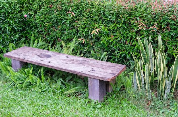 Kleine houten bank bij de struiken om uit te rusten in de achtertuin. Premium Foto