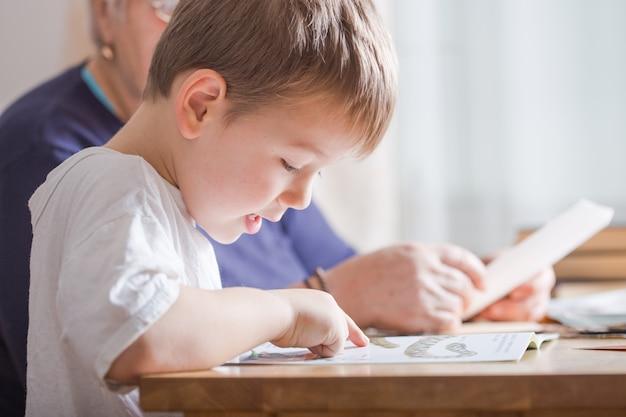 Kleine jongen 4 jaar oud leesboek. hij zit op een stoel in de zonnige woonkamer en kijkt naar foto's in een verhaal. kid huiswerk voor basisschool of kleuterschool. kinderen studeren. Premium Foto